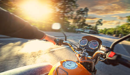 Motorcyclist drives motorbike on a sunny day on the street Imagens