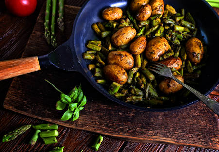 Potatoes fried with asparagus in a pan with spices Фото со стока