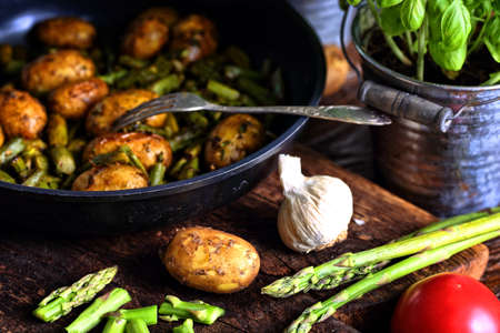 Potatoes fried with asparagus in a pan with spices and tomatoes