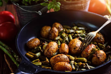 Potatoes fried with asparagus in a pan