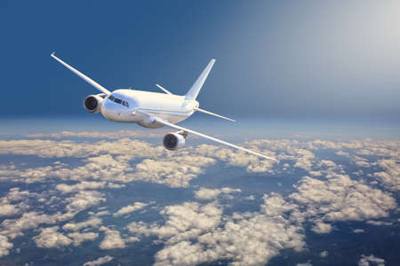 passenger plane is flying high above the clouds