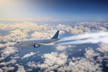 passenger plane is flying above the clouds