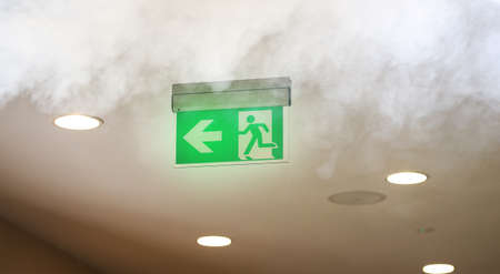 Evacuating sign in office builging while fire Stockfoto