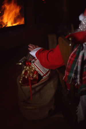 Santa Claus with presents sits in front of the fireplace