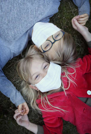 Young kids are lying on the grass with facial masks Stock fotó