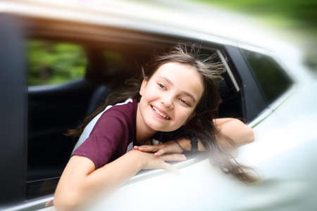 smiling brunette teenage girl is driving the car