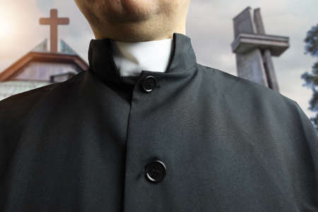 priest in a cassock in front of the church