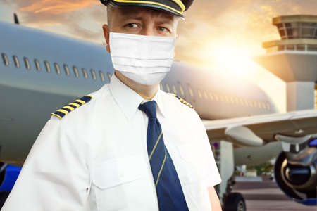 Airplane captain pilot in mask on airport 免版税图像