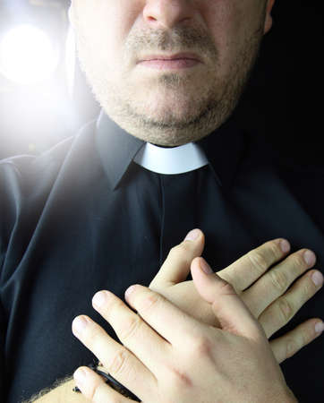A priest holds folded hands against black