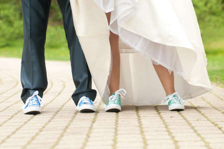 Bride and groom in color gym shoes Stock Photo