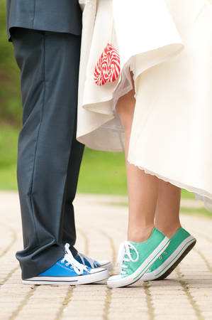 Bride and groom in gym shoes with lollipopp