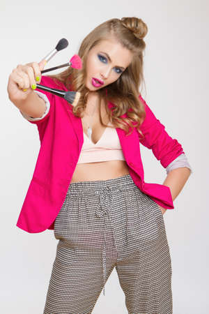 Beautiful fashionable girl with long curly hair in a pink jacket. Girl in the studio on a grey background holding brushes for make-up.