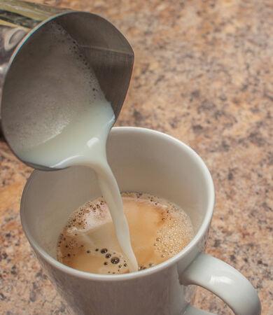 Mixing of Milk and Espresso Фото со стока
