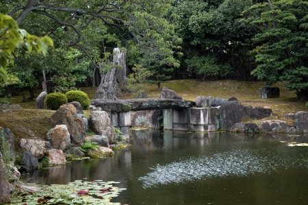 taş köprü kayalar ve lotus çiçekleri ile Japon bahçe Stock Photo