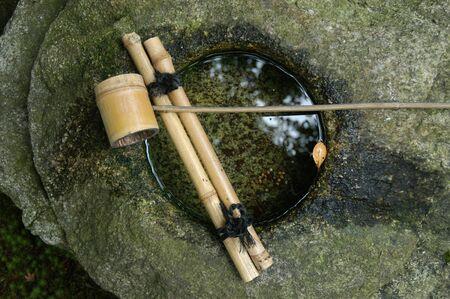 Bambu pota ve su ile tsukubai taş havzası Stock Photo