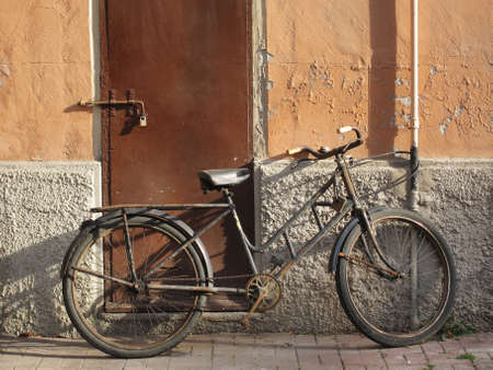 abandoned old rusty bicycle leaning against a wall Stock Photo