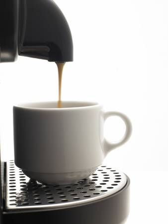 Detail on a white background a coffee machine with cup