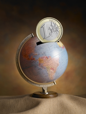 globe, map of the earth, made   as a money box, with euro coins on warm backdrop