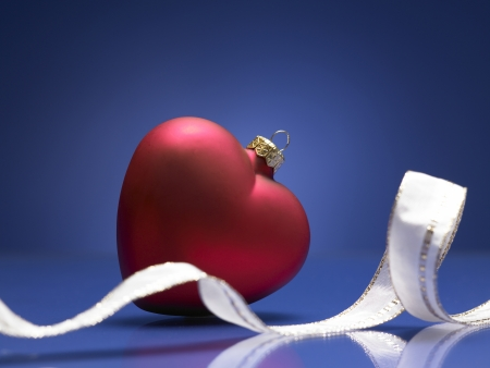 red christmas ball in shape of heart on a blue background
