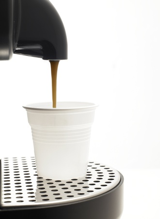 Detail on a white background a coffee machine with plastic cup Stock Photo