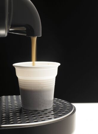 Detail on black background a coffee machine with plastic cup Stock Photo