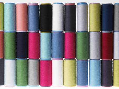 Spools of thread colored geometric composition on a white background