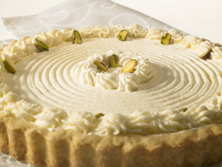 Rare Cheese Tart with pistachio nuts and whipped cream, on a white background Stock Photo