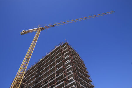arise: construction site with tower crane and blue sky