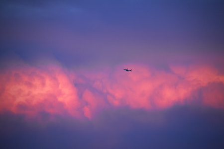 airliner flying in the sky with red clouds at sunset