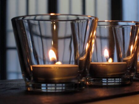 lit candles in glasses on rustic wooden shelves Stock Photo