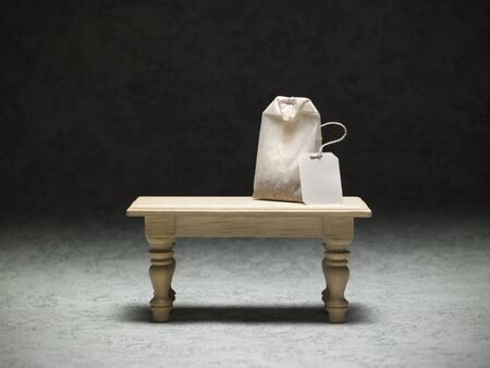 miniature table with a tea bag on dark background