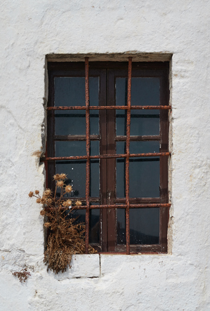 Old closed window with iron bars and white wall