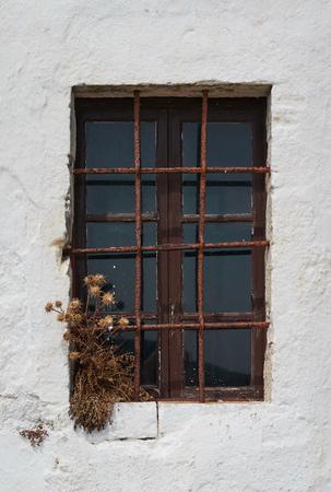 rejas de hierro: Vieja ventana cerrada con barras de hierro y pared blanca