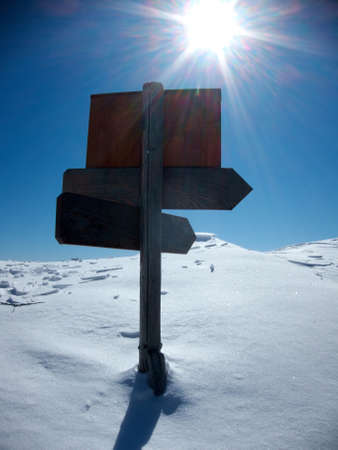 wooden signs on mountain path snow covered and glare of the sun in the sky Stock Photo
