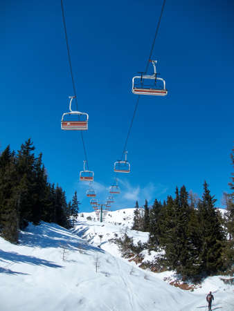 chairlift with orange seats on blue sky, snow-covered mountain
