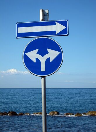 blue signs for directions on background with sea and sky