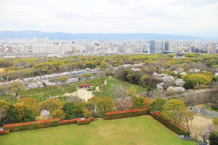 arial views: Arial view of sky, mountains, buildings, trees, and fields in Osaka, Japan Editorial