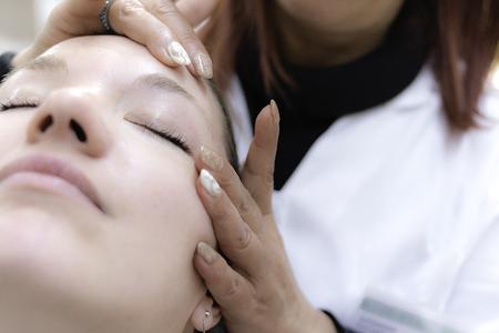 若い女性は彼女の顔にマッサージでリラックスします。