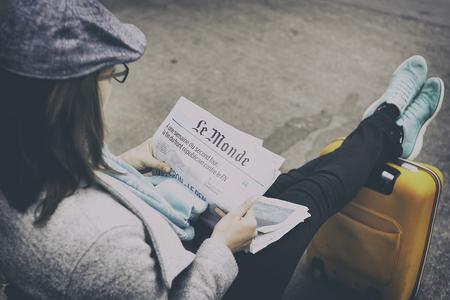 フランスの新聞ル ・ モンド フランス語大統領の最初のラウンドの後の日を読んでパリ, フランス - 2017年 4 月: 女性。出発の準備ができて、彼女のス