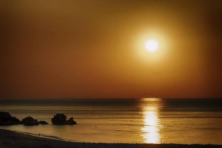 海の上の岩と美しい夕日 写真素材