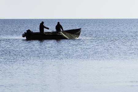 青い海で網を引く人の漁師