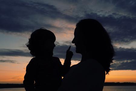 幸せな家族のシルエット、母と娘を踏んで美しい夕日