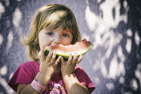スイカを食べた幸せな赤ちゃん 写真素材