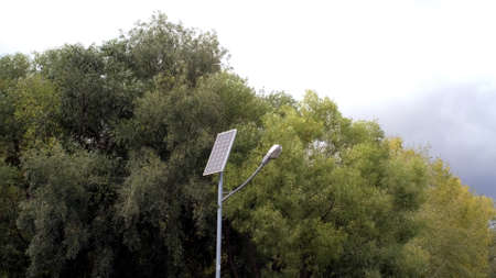 Saving technology. Green energy. Clean energy. Street lamp post with solar panel in Park with green tree and blue sky for background energy saving concept. Clean energy. Standard-Bild - 147041451