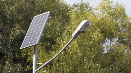 Green energy. Saving technology. Street lamp post with solar panel in Park with green tree and blue sky for background energy saving concept. Clean energy. Nature protection.