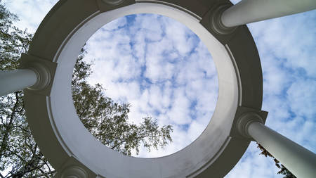 View of the sky through the ceiling of the rotunda. Hole in the ceiling. Beautiful white stone baroque large alcove with columns. Antique architecture.