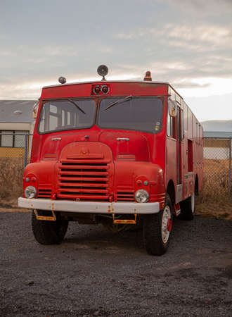 Historic red fire engine in a parking lot in Reykjavik, Iceland. Retro car in perfect condition. Automotive equipment. Vertical photo.