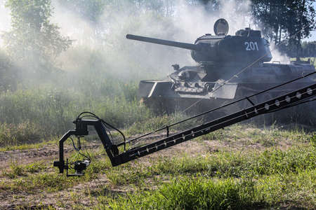 Filming a tank shrouded in smoke. Soviet tank t-34 on the move. Cameras filming the tank. A war scene of a tank with a smoking turret.