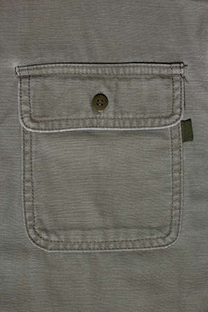 Denim background made of khaki denim textiles. On the pocket is sewn a tag for applying text or logo. Military clothing. Shirt for tourism. Military uniform.