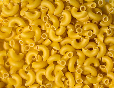 Texture of pasta in the form of an arc. Pasta close-up twisted horns. Raw pasta heart shaped horns.
